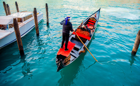 Gondolier in straw hat goes on paddle ship trip with passengers, next to blue water moored white boat venice