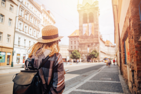 Young woman tourist in straw hat and backpack uses phone as navigator through streets of Europe. Stock Photo