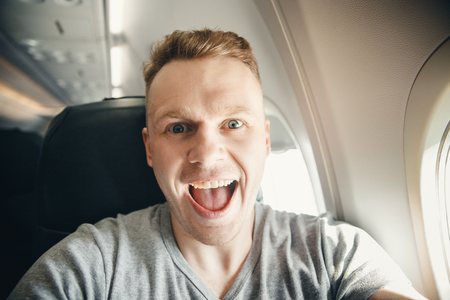 Happy tourist man makes selfie photo in cabin aircraft airplane before departure. Travel concept.