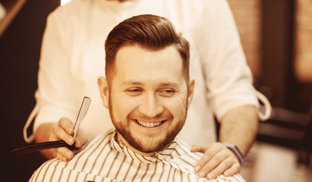 Barber man shaves his beard and cuts hair to client in barbershop. Stockfoto