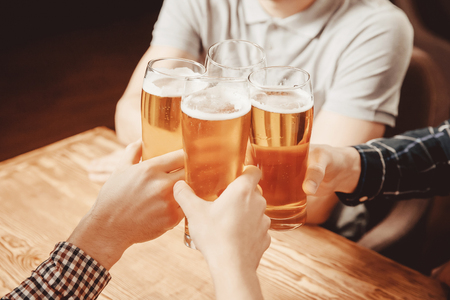 Irish pub. Men hands with glasses of beer in frame close up. Bearded guy white Polo background Stock Photo
