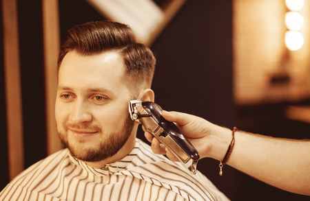 Hipster with fashionable haircut, beard trim temples barbershop electric razor