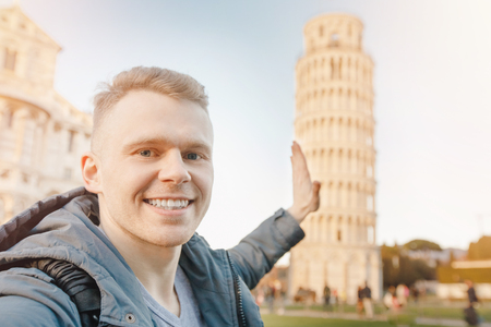 Happy male traveler makes selfie photo on background Leaning Tower of Pisa.