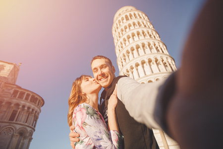 Travel concept. Loving happy couple takes selfie photo on stick and camera against background of leaning Tower Pisa, Italy