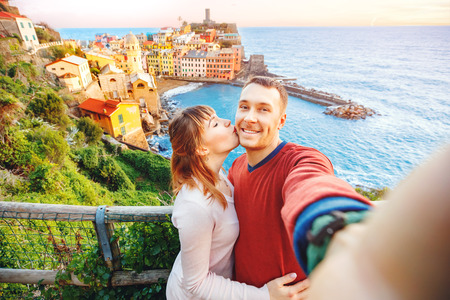 Tourists happy couple taking selfie photo of Vernazza, national park Cinque Terre, Liguria, Italy, Europe. Concept travel.