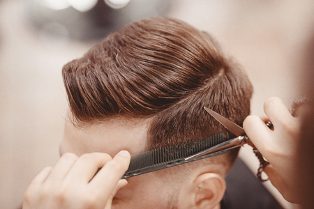 Close-up, master hairdresser does hairstyle with scissors comb. Concept Barbershop. Banco de Imagens