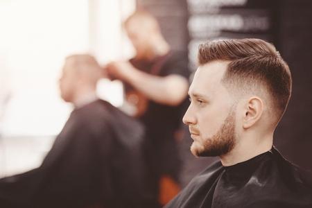 Banner de barbería. Hombre en silla de peluquero, peluquero peinando su cabello Foto de archivo