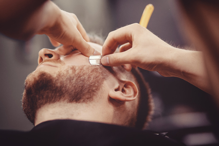 Man Barber shaves beard of client on chair Barbershop.