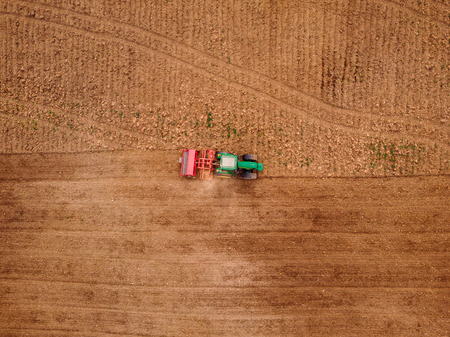 Agriculture tractor plows field of land for sowing. Top view aerial photo