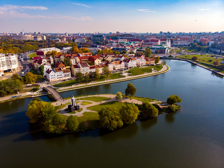 Green island of tears in middle river bridge from which leads to old historic district with houses red roofs on Sunny autumn day. Minsk, Republic Belarus. Top view aerial drone