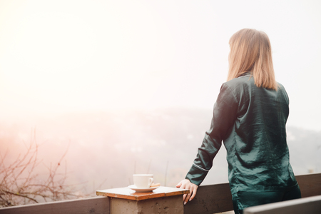 Beautiful young woman with cup coffee on terrace in green pajamas meets morning.