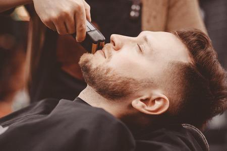 Kapper scheert baard van cliënt man op stoel Barbershop.