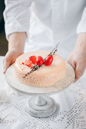 Male chef puts Easter cake kulich with chocolate eggs and willow on table.