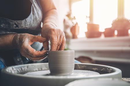 De tovenaar met gerimpelde handen op het pottenbakkerswiel maakt kleischotels. Plek om te werken.