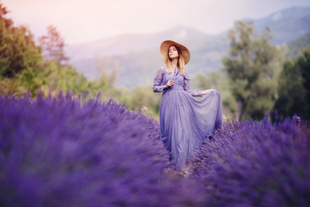 Beautiful girl in long purple dress walks among lavender fields, France, Provence. Foreground and background with mountains blurred