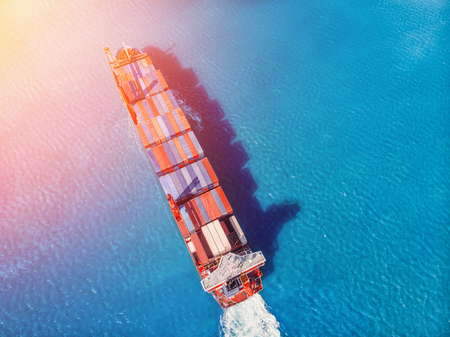 Logistics transportation of International container cargo ship in blue ocean. Top view aerial. Concept Shipping.
