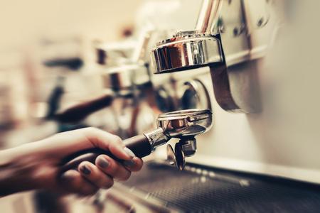 Jonge barista vrouw bereidt koffiemachine voor het maken van espresso. Tamper Filter houder