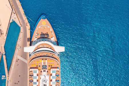 Cruise liner luxury ship in berth in port, blue sea water. Top aerial view.