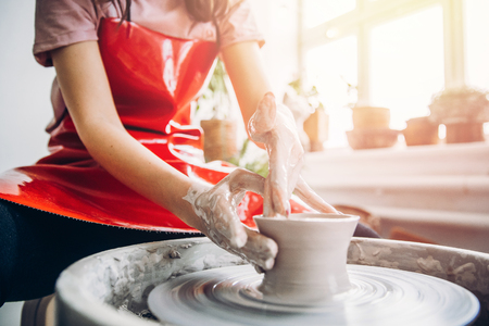Mujer joven en delantal rojo trabaja detrás de la rueda de alfarero con longitud, haciendo placa hecha a mano. Concepto de concentración, creatividad hecha a mano.