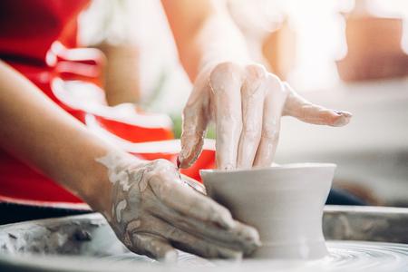Jonge vrouw in rode schort werkt achter pottenbakkerswiel met lengte, handgemaakte plaat maken. Concept van concentratie, creativiteit met de hand gemaakt. Stockfoto