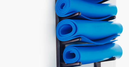 Blue yoga mat attached white wall in stack. Concept tool for practicing Hatha Stock Photo