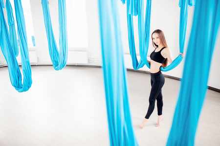 Aerial fly yoga in white gym. Young beautiful women practicing stretching pilates in blue hammock