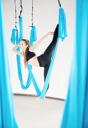 Aerial fly yoga in white gym, young gymnastics women in blue hammock Banco de Imagens