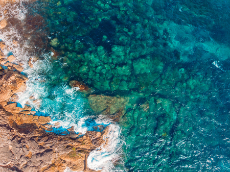 Coast of desert island with blue turquoise water beats on rocky reef. Aerial top view. Stockfoto