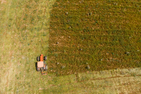 Aerial top view agriculture, tractor removes mowing green grass field