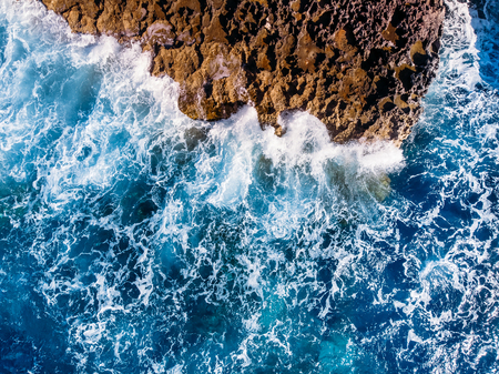 Top view Azure blue sea with waves beating on beach and rocks. Aerial photo. Reklamní fotografie