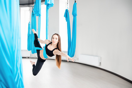 Young beautiful women gymnast in blue hammock. Aerial fly yoga in white studio