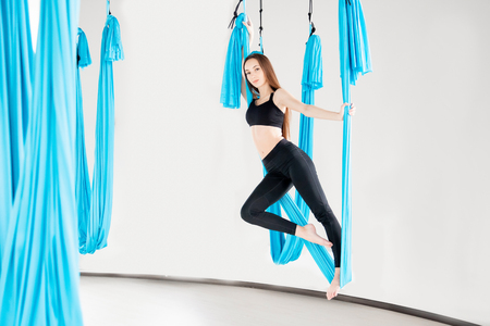 Aerial fly yoga young beautiful women gymnast in blue hammock