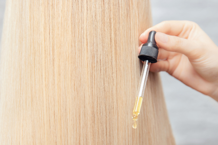 Close-up drop of oil restore and recovery hair is applied to head bulbs. Concept hairdresser spa salon Banco de Imagens