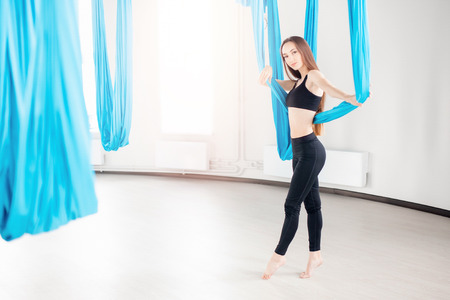 Aerial fly yoga in white studio. Young beautiful women. Copy space