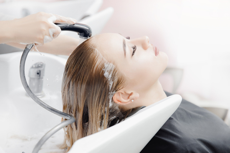 Beautiful blond woman getting hair wash in beauty salon. Concept head treatment care Reklamní fotografie - 124816947