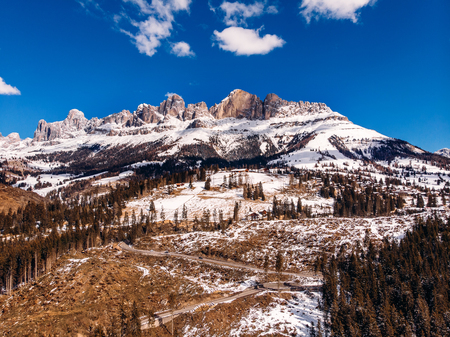 Deforestation in Alps mountains, Italy. Felled tree trunks on background of Dolomites. Aerial view Stock Photo