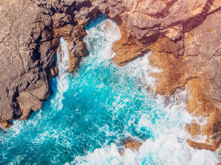 Top view Azure blue sea with waves beating on beach and rocks. Aerial photo. Stockfoto