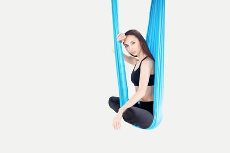 Young woman performing antigravity aerial yoga exercise in white studio. Concept meditation Banco de Imagens