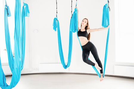 Young woman performing antigravity aerial yoga exercise in white studio Banco de Imagens - 124817466