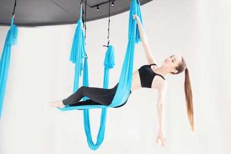 Young woman performing antigravity aerial yoga exercise in white studio. Concept meditation Stockfoto