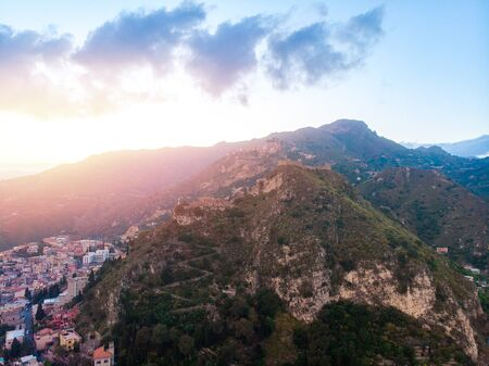 Taormina, Sicily Italy sunset, volcano Etna in clouds. Aerial top view, drone photo