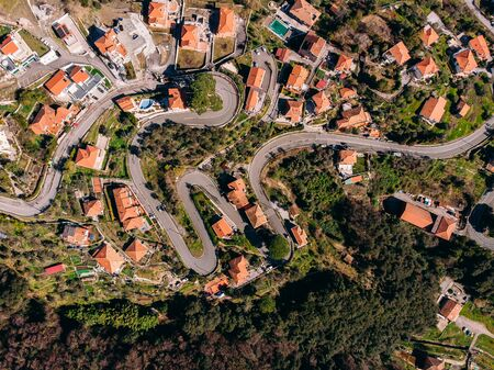 Winding mountain road to bends, Houses with tiled red roof, swimming pool and garage. Aerial top view