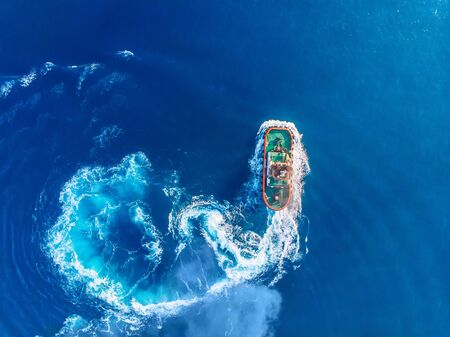 Tugboat blue sea port. Aerial top view Banco de Imagens