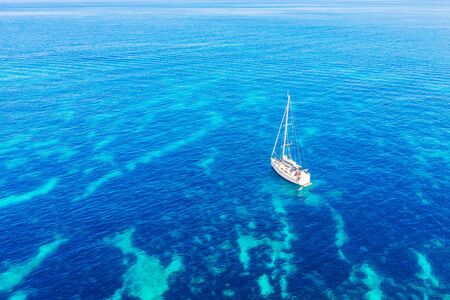 Aerial top view pleasure white yacht with sail blue transparent turquoise water sea. Concept travel Zdjęcie Seryjne