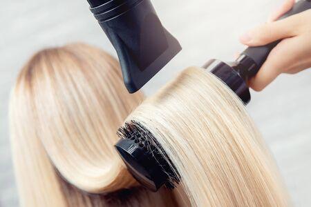 Primer plano de secador de pelo, salón de corte de concepto, estilista femenina