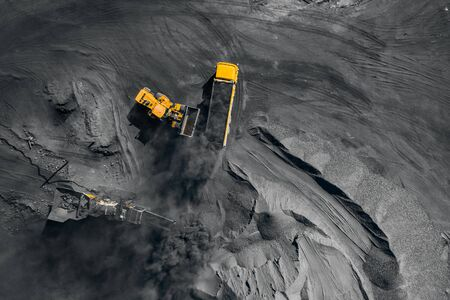 Open pit mine, coal loading in trucks, transportation and logistics, top view aerial