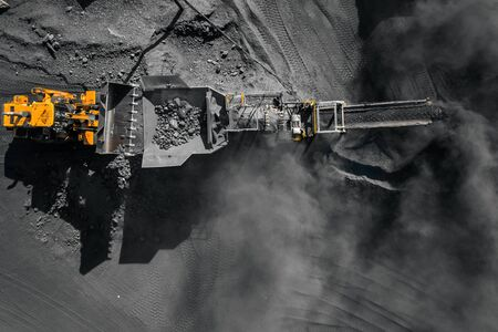 Open pit mine, excavator loads coal to crushing machine, chopper and sorting, top view aerial drone 写真素材