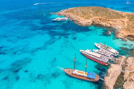 Concept paradise vacation. White yacht with sail in clear water of sea with sand. Blue Lagoon Comino Malta. Aerial view