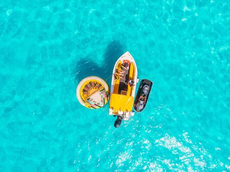 Pleasure wooden ship with mast in clear blue sea. Aerial view.