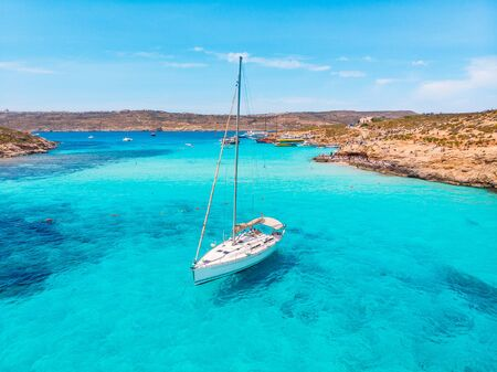 White yacht stands in azure transparent water sea, beach Blue Lagoon Comino Malta. Aerial view
